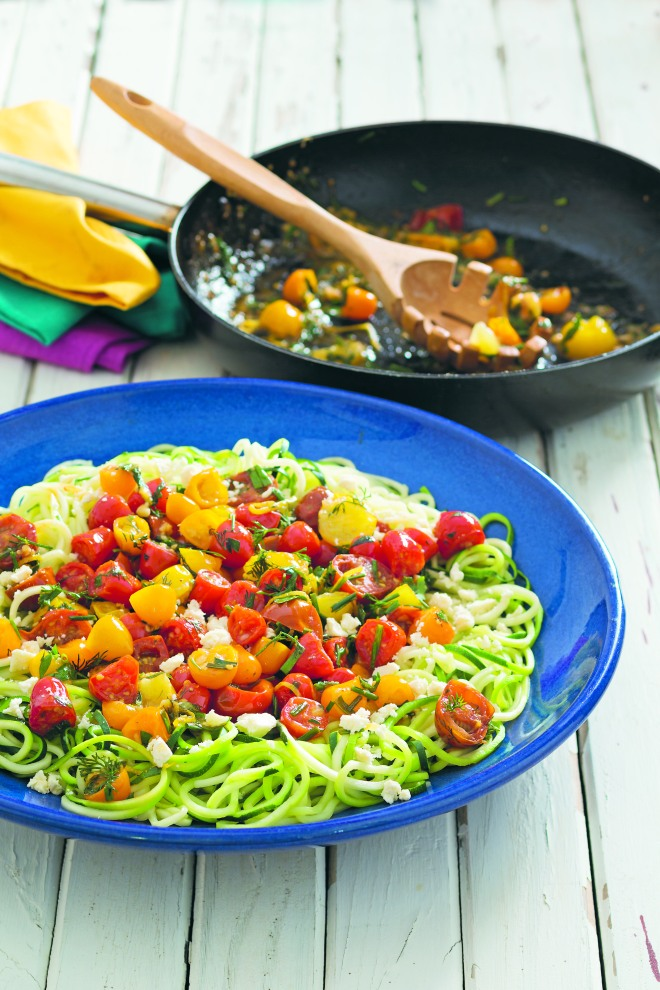 Zucchini noodles with herby cherry tomatoes, lemon & feta • SERVES 4 • If wheat-based pasta leaves you feeling bloated and tired, improvise with zucchini noodles instead. I recently made this for my family to change things up and now it's our preferred option. (You can make the noodles with a sharp potato peeler and knife but I highly recommend investing in a spiral vegetable cutter.) 3 zucchini (courgettes), about 750 g (1 lb 10 oz) 3 tablespoons olive oil 4–5 garlic cloves, finely chopped 700 g (1 lb 9 oz) medley cherry tomatoes, halved zest and juice of ½ lemon 1 handful of flat-leaf (Italian) parsley leaves, chopped 1 handful of dill, chopped 1 handful of sweet marjoram leaves, chopped 20 g (¾ oz/1 small bunch) chives, finely chopped 120 g (4¼ oz) Greek feta cheese, crumbled Cut the zucchini into manageable pieces for a spiral vegetable cutter. Make noodles according to the manufacturer's instructions. Bring a large saucepan half-full of water to the boil. Set a large colander over the top of the boiling water, put in the zucchini noodles, cover with a well-fitting lid and steam for 5–7 minutes until al dente. Don't overcook the noodles or they will lose their shape and break. Meanwhile heat the oil in a large frying pan over low heat. Gently fry the garlic for 1 minute, or until soft. Toss in the tomatoes, increase the heat to high and cook for 3 minutes, stirring occasionally to ensure even cooking. Add the lemon zest and juice, the herbs and season with salt and pepper. Cook for a further 3 minutes, or until the tomatoes blister and are heated through. Strain the zucchini noodles, as they retain water. Serve the herby tomatoes over the zucchini noodles, topped with the crumbled feta.